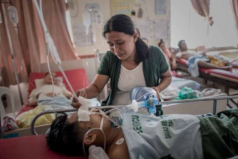 A typhoon victim checks on her husband as she keeps him alive by manually pumping air into his lungs following his leg amputation that led to an infection, at the Divine Word hospital which still operates without electrical power on the 7th day of the Typhoon Haiyan disaster in Tacloban, on the eastern island of Leyte on November 15, 2013. The United Nations has confirmed at least 4,500 killed in the disaster, which brought five-meter (16-foot) waves to Tacloban, flattening nearly everything in their path as they swept hundreds of meters across the low-lying land. (Philippe Lopez/AFP/Getty Images)