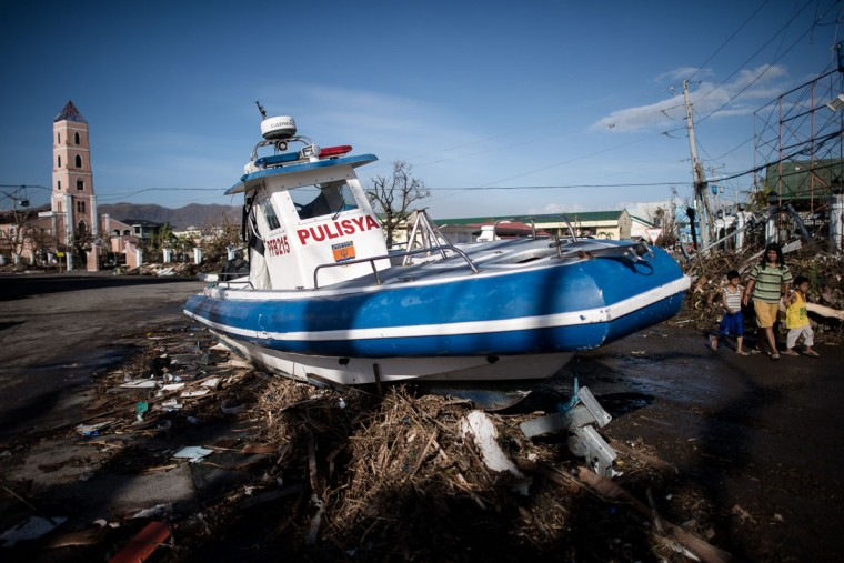 A boat washed ashore stands in the middle of a crossroad on the 7th day of the Typhoon Haiyan disaster in Tacloban, on the eastern island of Leyte on November 15, 2013. The United Nations estimates 10,000 people may have died in Tacloban alone, where five-metre (16-foot) waves flattened nearly everything in their path as they swept hundreds of metres across the low-lying land. (Philippe Lopez/AFP/Getty Images)