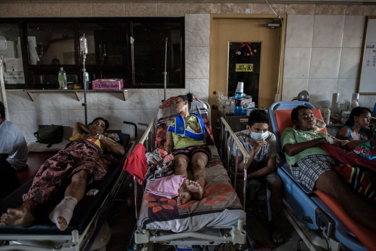 Typhoon victims are treated in the lobby of the Divine Word hospital, lacking electrical power on the 7th day of the Typhoon Haiyan disaster in Tacloban, on the eastern island of Leyte on November 15, 2013. The United Nations estimates 10,000 people may have died in Tacloban alone, where five-metre (16-foot) waves flattened nearly everything in their path as they swept hundreds of metres across the low-lying land. (Philippe Lopez/AFP/Getty Images)