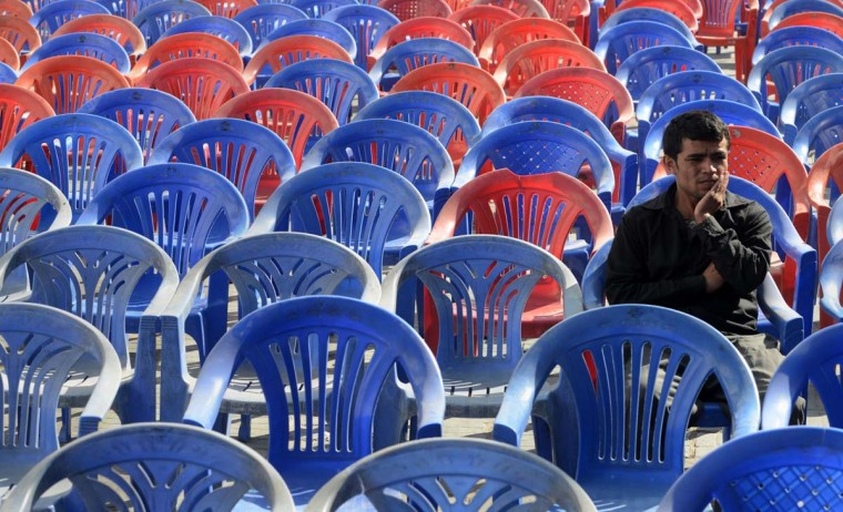 A supporter of the Unified Communist Party of Nepal (Maoist) chairman Pushpa Kamal Dahal, also known as 'Prachanda', waits to listen to him speak at an election campaign rally in Kathmandu on November 15, 2013. Nepal's election is scheduled for November 19. More than 100 parties, including three major ones -- the Unified Marxist-Leninist, the Nepali Congress and the Maoists -- are fielding candidates for the 601-seat parliament, which is also expected to act as a constitution-drafting body. (PRAKASH MATHEMA AFP/Getty)