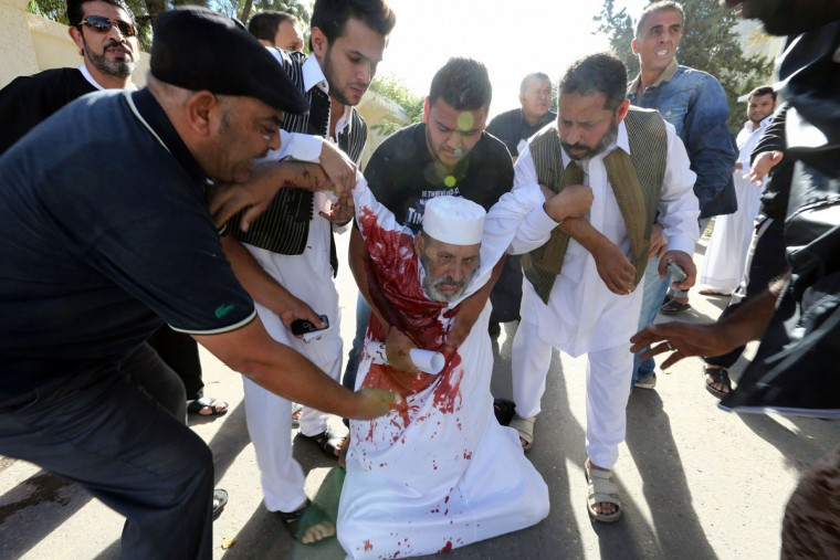 People assist a man who was injured after Libyan militiamen opened fire on a crowd wanting them to move out of their headquarters on November 15, 2013 in southern Tripoli. Gunmen started firing at a peaceful crowd demonstrating in the capital's Meliana Square when people approached the building. (Muhmad Turkiamah/AFP/Getty Images)