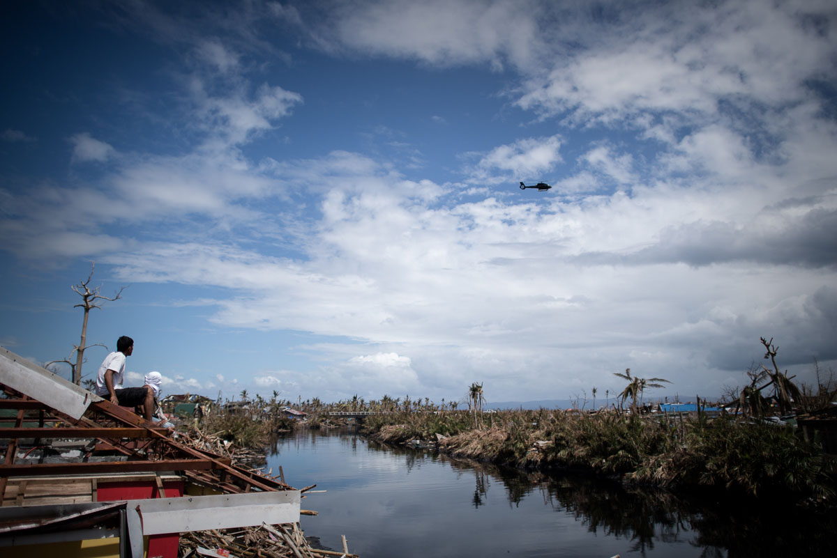 A survivor of Typhoon Haiyan (L) sits on a destroyed rooftop as a helicopter flies by in Tanauan, on the eastern island of Leyte on November 16, 2013. Spearheaded by a US aircraft carrier group, foreign relief efforts have stepped up a gear in the storm-devastated Philippines eight days after Super Typhoon Haiyan left thousands dead and millions homeless. (Philippe Lopez/AFP/Getty Images)