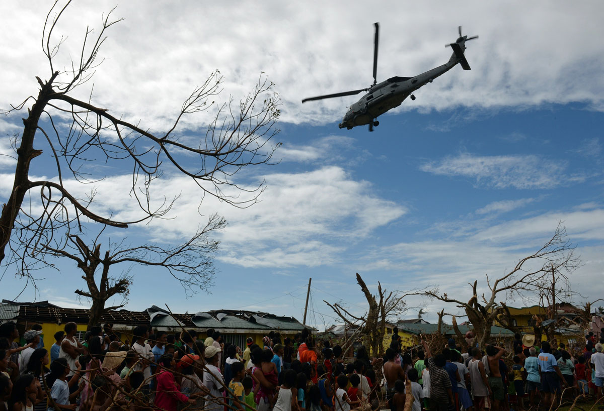 Residents watch as a US navy seahawk helicopter which dropped off relief goods hovers above the town of Giporlos, Eastern Samar province, central Philippines on November 16, 2013. Spearheaded by a US aircraft carrier group, foreign relief efforts have stepped up a gear in the storm-devastated Philippines eight days after Super Typhoon Haiyan left thousands dead and millions homeless. (Ted Aljibeted/AFP/Getty Images)