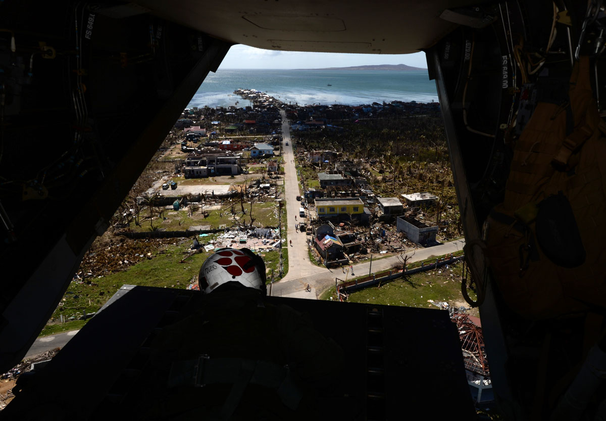 A crewman from a US Marines Osprey aircraft flies over a town devastated by Typhoon Haiyan near Balangiga City, Samar Province on November 16, 2013. Spearheaded by a US aircraft carrier group, foreign relief efforts have stepped up a gear in the storm-devastated Philippines eight days after Super Typhoon Haiyan left thousands dead and millions homeless. (Mark Ralston/AFP/Getty Images)