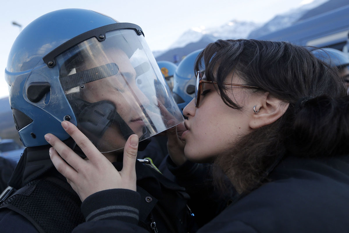 A demonstrator kisses a riot police officer on November 16, 2013 during a protest in Susa against the high-speed train (TAV in Italian) line between Lyon and Turin. The link, expected to come into service in 2025, will see one million fewer trucks on the highways a year, and reduce train times between Paris and Milan from seven hours to just over four. (Marco Bertorello/AFP/Getty Images)