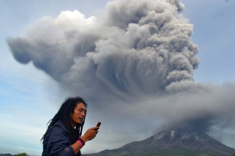 A man uses his mobile phone as Mount Sinabung continues to erupt, with hot smoke spewing from the volcano, in the Karo district on the north of Indonesia's Sumatra island on November 18, 2013. Officials said a week ago at more than 5,000 people had fled their homes since the volcano erupted early this month. (Sutanta Aditya/AFP/Getty Images)