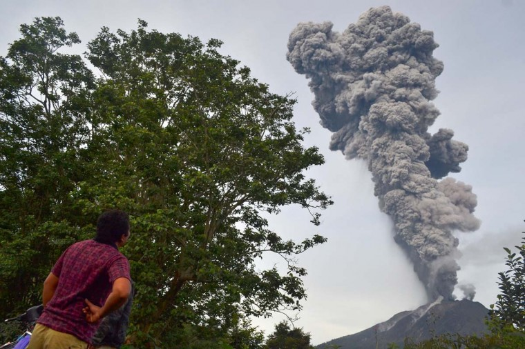 A man watches as Mount Sinabung continues to erupt, with hot smoke spewing from the volcano, in the Karo district on the north of Indonesia's Sumatra island on November 18, 2013. Officials said a week ago at more than 5,000 people had fled their homes since the volcano erupted early this month. (Sutanta Aditya/AFP/Getty Images)
