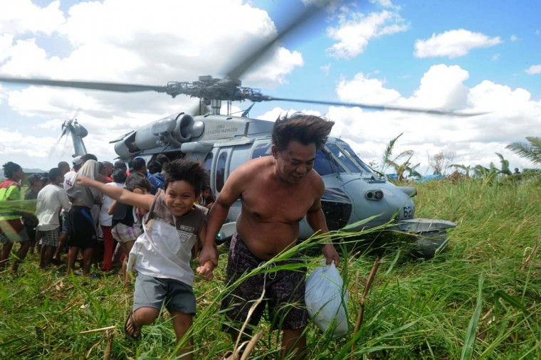 A US Navy helicopter delivers relief goods to typhoon victims in the aftermath of typhoon Haiyan in Ormoc, on the eastern island of Leyte on November 18, 2013. Philippine President Benigno Aquino on November 18 blamed the slow response to the ravages of Typhoon Haiyan on the total collapse of local government in the face of the storm's unprecedented destructive power. (Noel Celis/AFP/Getty Images)