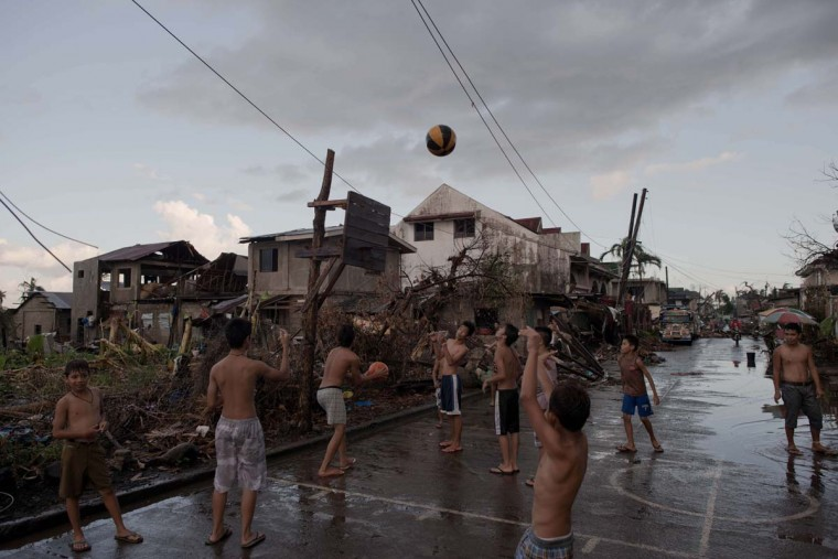 Typhoon victims play basketball with a hoop made out of wood from destroyed houses in Jaro on November 18, 2013. The United Nations has confirmed at least 4,500 killed in the disaster, which brought five-metre (16-foot) waves to Tacloban, flattening nearly everything in their path as they swept hundreds of metres across the low-lying land. (Nicolas Asfouri/AFP/Getty Images)