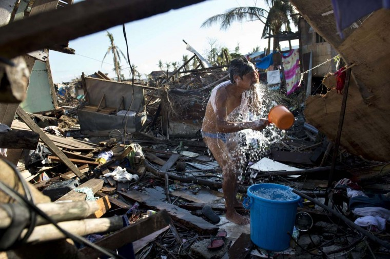 Joe (no last name given) washes in the rubble of what used be his house in Tacloban on November 18, 2013. Grieving survivors of a monster typhoon that smashed into the mainly Catholic Philippines flocked to shattered churches, as aid workers intensified efforts to reach desperate survivors in remote communities. (Odd Andersen/AFP/Getty Images)
