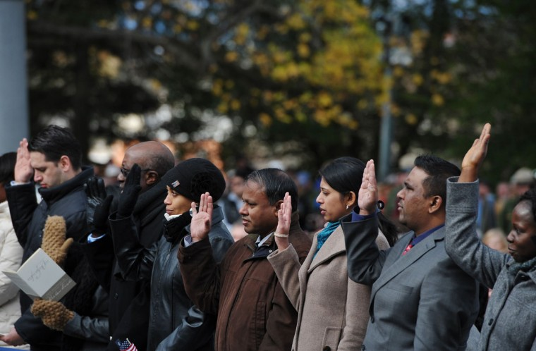 People raise their hands as they take part in a naturalization ceremony to become US citizens during the commemoration ceremony of the 150th anniversary of US President Abraham Lincolns historic Gettysburg Address on November 19, 2013 at Gettysburg National Military Park in Gettysburg, Pennsylvania. (Mandel Ngan/AFP/Getty Images)