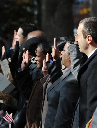 People raise their hands as they take part in a naturalization ceremony to become US citizens during the commemoration ceremony of the 150th anniversary of US President Abraham Lincolns historic Gettysburg Address on November 19, 2013 at Gettysburg National Military Park in Gettysburg, Pa. (Mandel Ngan/AFP/Getty Images)