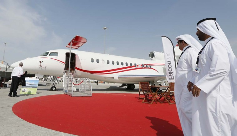 "Men look at a Falcon 7X airplane during the Dubai Airshow on November 18, 2013 in Dubai. The city this week is set to host more than 2,000 officials for a different kind of trade gathering, according to The Malaysian Insider: The emirate will try to become the center of an ""Islamic Economy"" where trade in halal goods and services is regulated, the paper reports."