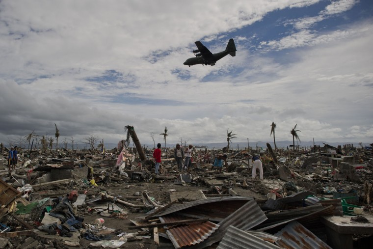 Super Typhoon Haiyan victims sift through the rubble of their destroyed homes as a military cargo plane flies over head in Tacoblan on November 20, 2013. The United Nations has confirmed at least 4,500 killed in the disaster, which brought five-metre (16-foot) waves to Tacloban, flattening nearly everything in their path as they swept hundreds of metres across the low-lying land. (Nicolas Asfouri/AFP/Getty Images)
