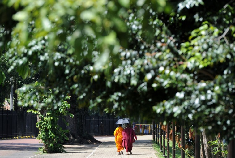 Sri Lankan Buddhist monks walk past the Temple of Tooth in the central town of Kandy on November 20, 2013. The shrine, a UNESCO world Heritage Site, is one of the most important places of worship for the island's Buddhist majority. (Lakruwan Wanniarachchi/AFP/Getty Images)