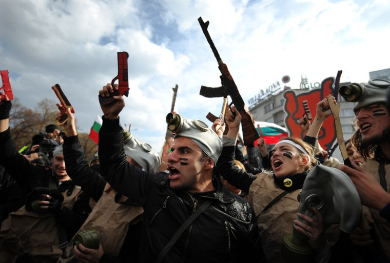 """Students with cardboard weapons participate in a performance during an anti-government protest in front of Bulgarian parliament in Sofia, on November 20, 2013. Shouts """"Resignation"""" and """"Victory"""" were also heard as a workers rally merged with the daily protest of about 1,000 students outside parliament, who pressed for Oresharski to go and demanded new morals in politics they saw as corrupt and catering too much for big business interest. Several thousand Bulgarian public sector workers rallied in Sofia on Wednesday with demands for more government measures to ease poverty, as angry students kept pressing for the cabinet's resignation. (Nikolay Doychinov/AFP/Getty Images)"""