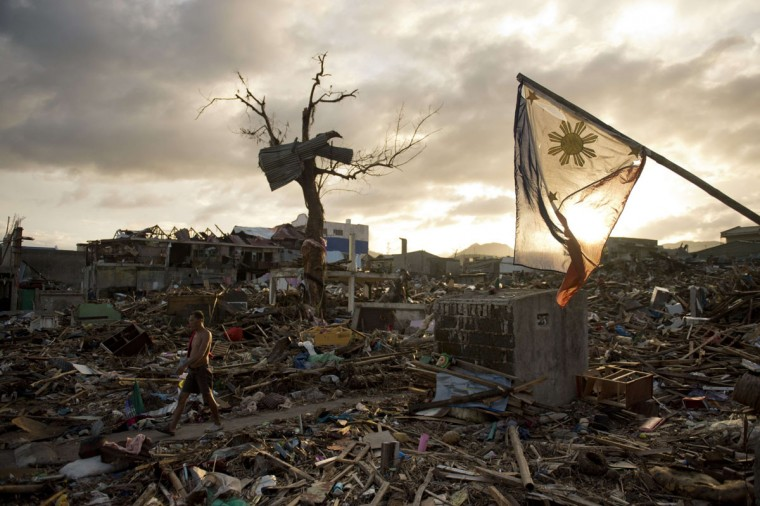 A man walks along as the national flag of the Philippines flies over the rubble of destroyed homes in Tacloban on November 20, 2013. More than 4,000 people were killed and up to 4.4 million displaced when typhoon Haiyan packing some of the strongest winds ever recorded by a storm made landfall. (Odd Andersen/AFP/Getty Images)