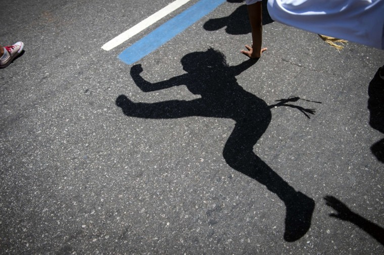 The shadow of a woman dancing Capoeira, a Brazilian martial art with elements of dance and acrobatics, is pictured during the Black Awareness Day in Rio de Janeiro, Brazil. (YASUYOSHI CHIBA / AFP/Getty Images)