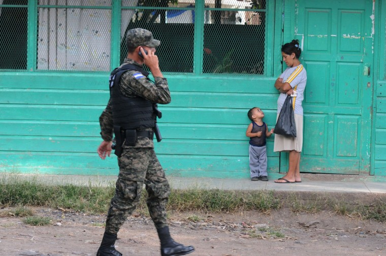 "A mother awaits for her child at the ""Jose Angel Ulloa"" school in Tegucigalpa. The school, which will be a voting station in Sundays' general election, is the base since three weeks ago of 100 men of the newly created Military Police who patrol the streets to fight delinquency. (ORLANDO SIERRA / AFP/Getty Images)"