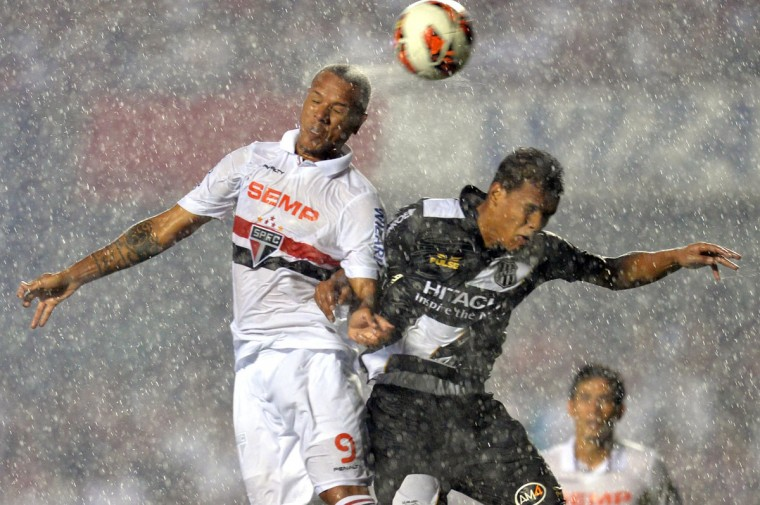 Luis Fabiano of Sao Paulo vies for the ball with Artur of Ponte Preta, during their 2013 Copa Sudamericana semifinal soccer match at Morumbi Stadium in Sao Paulo, Brazil. (NELSON ALMEIDA / AFP/Getty Images)