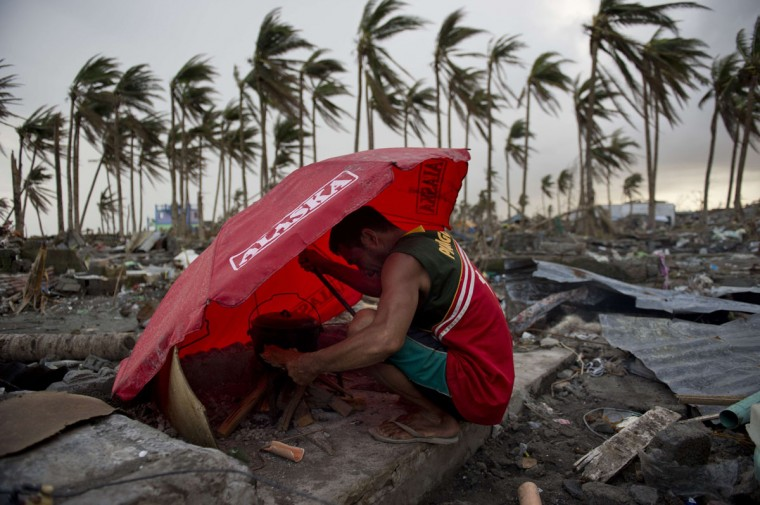 A man uses an umbrella to shelter from the wind as he tries to light a fire amid the rubble of destroyed homes in Tacloban, Philippines. (ODD ANDERSEN / AFP/Getty Images)