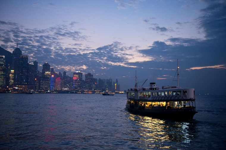 """Commuters travel on the Star Ferry (R) in Victoria Harbour from Kowloon to Hong Kong island (background) on November 21, 2013. Hong Kong's economy grew """"moderately"""" year-on-year in the third quarter as domestic demand and """"resilient"""" growth in the mainland Chinese market offset a weaker environment in the West, officials said on November 15. (Anthony Wallace/AFP/Getty Images)"""