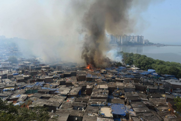 The Indian Ambedkar Nagar slum is seen on fire in Mumbai. Several huts were gutted in a fire that broke out in the settlement adjacent to the World Trade Centre building. (INDRANIL MUKHERJEE / AFP/Getty Images)