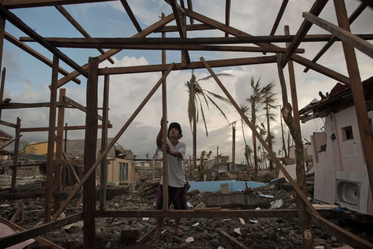 A typhoon victim constructs his new home in Palo, Philippines. (NICOLAS ASFOURI / AFP/Getty Images)