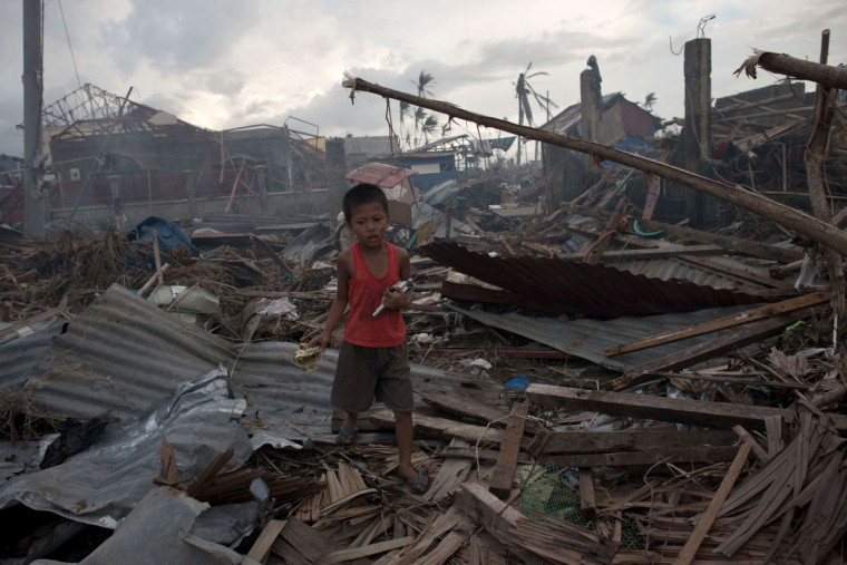 A young typhoon survivor holds broken toys found amidst the rubble in Palo, Philippines. (NICOLAS ASFOURI / AFP/Getty Images)