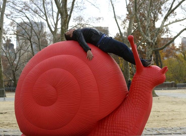 "Kevin Radtke from Cologne , Germany poses for pictures for a friend on a Red Snail Sculpture at the Rumsey Playfield in Central Park in New York on November 21. Galleria Ca d'Oro and Villa Firenze Foundation as presenting ""Eight Giant Red Snails"" as part of the REgeneration Art Project. The red snails inhabit Central Park from November 9 through December 3 before moving to Columbus Circle from December 5 to January 6, 2014. TIMOTHY CLARY/AFP/Getty Images ORG"