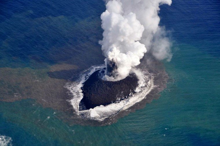 This handout picture taken by the Japan Coast Guard on November 21, 2013 shows white smoke rising from a newly created islet from a volcano near the Ogasawara island chain in Japanese waters, 1,000 kms (600 miles) south of Tokyo. Video footage showed plumes of smoke and ash billowing from the 200-metre island, and Japan's coast guard said it was warning vessels to use caution in the area until the eruption cools off. (Japan Coast Guard)