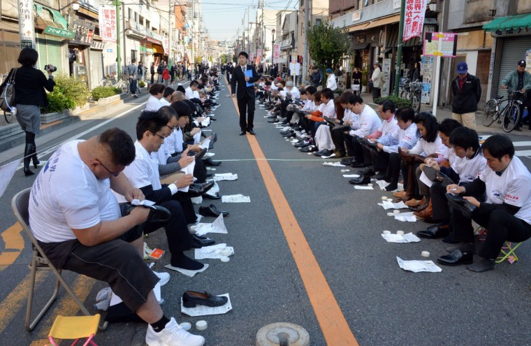 """Some 800 participants polish their leather shoes on a street in Tokyo's Taito ward, a district famous for its shoemakers in Japan, to challenge the record of """"most people polishing shoes"""" for the Guinness Book of World Records on November 22, 2013. Participants established a new world record over the previous one, made with 451 people in the UAE in 2011. (Yoshikazu Tsunoyo/AFP/Getty Images)"""
