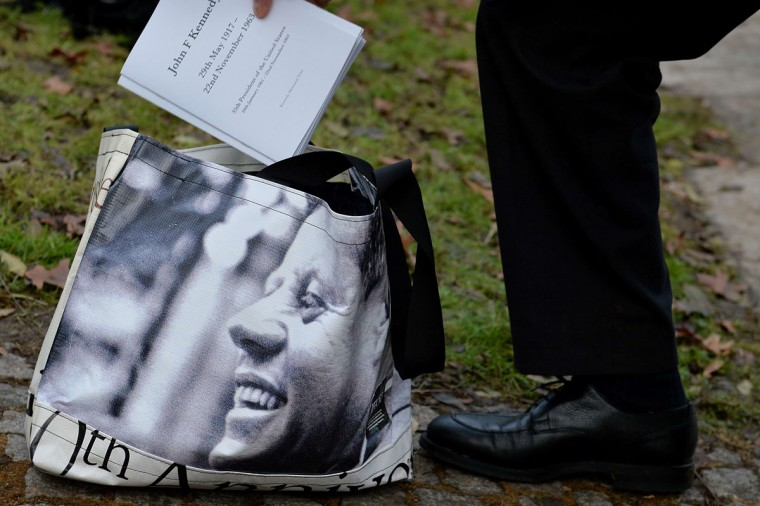 An organiser removes orders of service from a bag displaying an image of former US President John F Kennedy ahead of a memorial service for in Runnymede, Surrey on November 22, 2013, to mark the 50th anniversary of his assassination. (Ben Stansall/AFP/Getty Images)