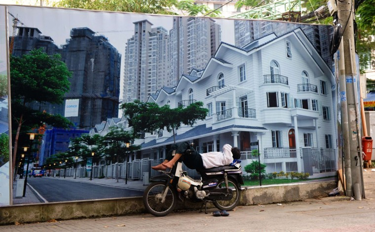 This picture taken on November 20, 2013 shows a motorbike taxi driver napping in front of a property advertising poster in downtown Ho Chi Minh city. The newly built luxury shopping mails and residential buildings in this Vietnam's largest city do underscore the gap between rich and poor in the Southeast communist nation. (Hoang Dinh Nam/AFP/Getty Images)