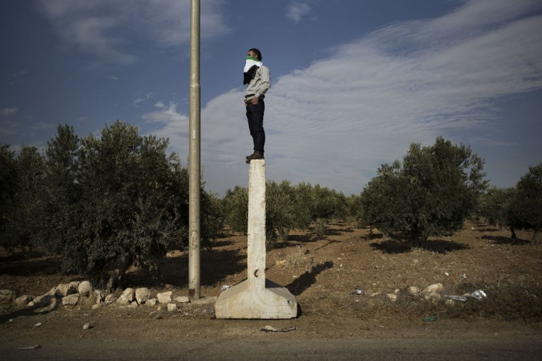 A Palestinian protester covers his face with a national flag as he stands on a concrete slab at a crossroad near the West Bank village of Tuqua on November 22, 2013, during a demonstration against Israeli settlers who set up tents at the main entrance of the village in protest against Palestinians attacking Israeli passing by cars. (Marco Longari/AFP/Getty Images )