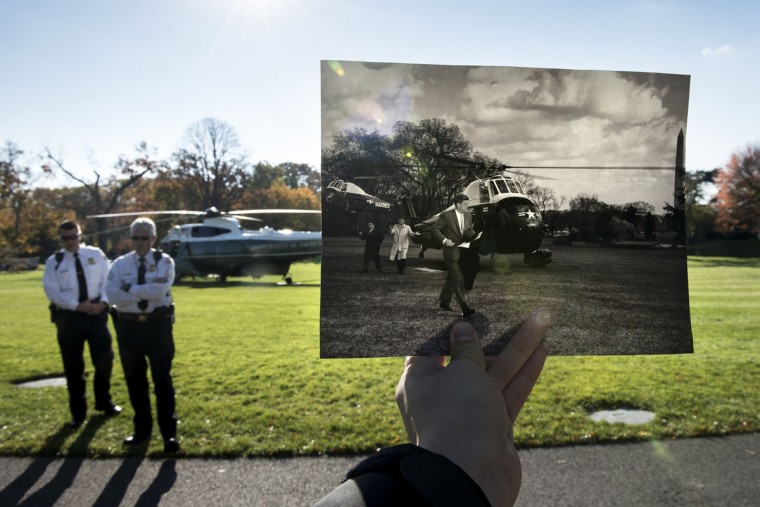 A historic photo (Robert Knudsen, White House Photographs, John F. Kennedy Presidential Library and Museum, Boston) showing former US President John F. Kennedy walking from transport helicopters is held up near its original location with a modern Marine One sitting in the background on the South Lawn of the White House November 8, 2013 in Washington, DC. The archive photo depicts Kennedy walking from both Army and Marine helicopters. At the time, both services shared responsibility for the US President's helicopter travels. November 22, 2013 marks the 50th anniversary of President John F. Kennedy's assassination in Dallas, Texas.