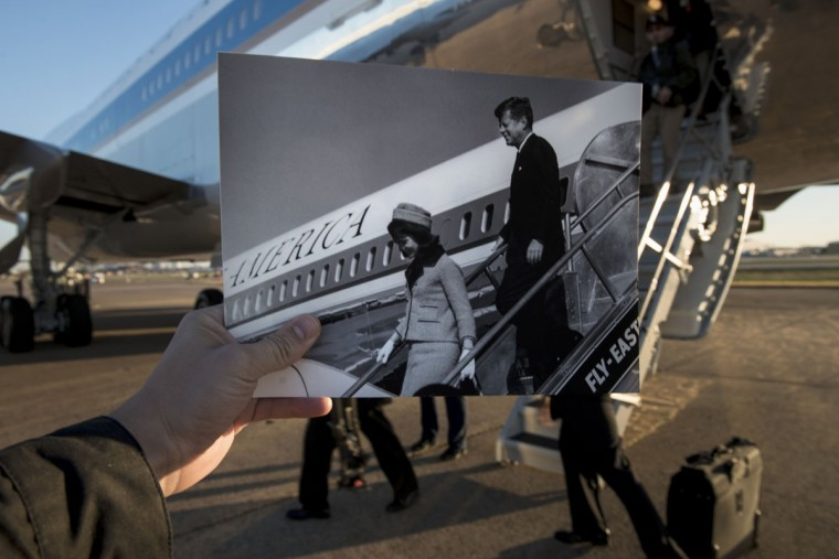 A historic photo dated November 22, 1963 showing former US President John F. Kennedy and First Lady Jacqueline Kennedy arriving in Dallas, Texas (Cecil Stoughton, White House Photographs, John F. Kennedy Presidential Library and Museum, Boston) is held up by the photographer against Air Force One in the background as US President Barack Obama arrives at Love Field November 6, 2013 in Dallas, Texas. The archive photo depicts the Kennedy's as they walk off an Air Force One based on the Boeing 707 as the modern Air Force One (seen in the current photograph) is based on the 747. November 22, 2013 marks the 50th anniversary of President John F. Kennedy's assassination in Dallas, Texas.