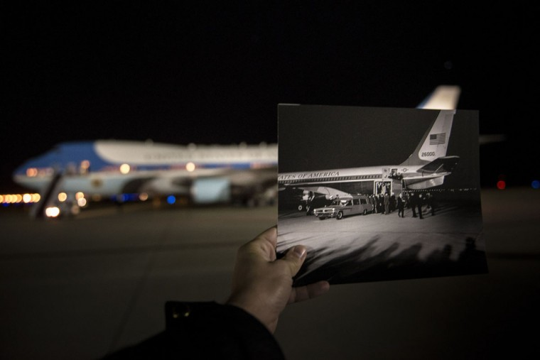 A historic photo dated November 22, 1963 (Cecil Stoughton, White House Photographs, John F. Kennedy Presidential Library and Museum, Boston) is held up by the photographer as Air Force One sits on the tarmac at Andrews Air Force Base, Maryland, November 6, 2013. The archive photo depicts President John F. Kennedy's remains being returned from Dallas, Texas and unloaded from Air Force One into a Navy Ambulance. November 22, 2013 marks the 50th anniversary of President John F. Kennedy's assassination.