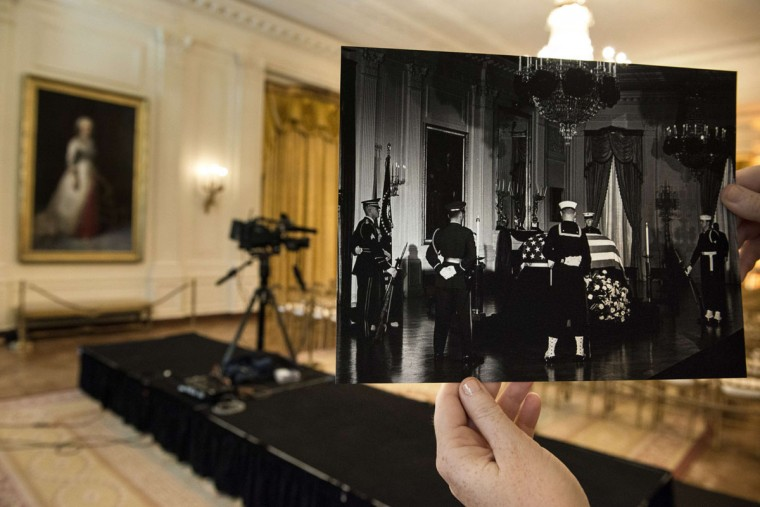 A historic photo dated November 23, 1963 (Robert Knudsen, White House Photographs, John F. Kennedy Presidential Library and Museum, Boston) is displayed near its original location in the Cross Hall of the White House November 8, 2013 in Washington, DC. The archive photo shows President John F. Kennedy's casket as it lies in state in the East Room of the White House attended by an honor guard. November 22, 2013 marks the 50th anniversary of President John F. Kennedy's assassination in Dallas, Texas.