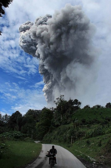 This picture taken on November 24, 3013 shows Sinabung volcano spewing volcanic ash in Karo. Several thousand people left their homes overnight, taking the total number of those who have fled since the volcano rumbled to life to around 12,300, said the national disaster agency. (Kharisma Tarigan/AFP/Getty Images)