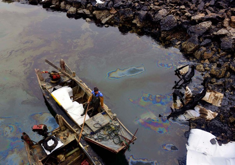 This picture taken on November 24, 2013 shows a worker cleaning up the oil slick on the river of Jiaozhou Bay after an oil pipeline exploded, ripping roads apart, turning cars over and sending thick black smoke billowing over the city of Qingdao, east China's Shandong province on November 22. The death toll from an oil pipeline explosion in a Chinese coastal city rose to 52 on November 24, as rain and the close proximity of dangerous gases hampered the rescue operation, state media said. (AFP/Getty Images)