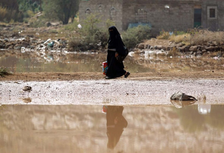 A Yemeni woman walks past puddles of flooded water following two days of rainfall on the outskirts of the capital Sanaa on November 25, 2013. (Mohammed Huwais/AFP/Getty Images)