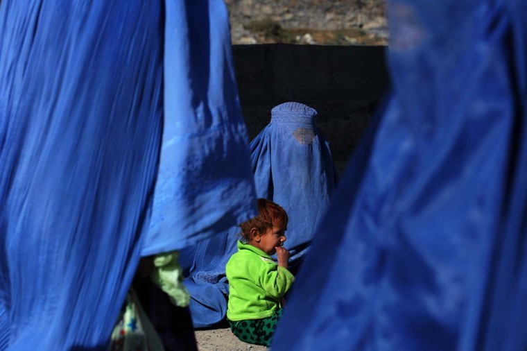 An Afghan child wearing a green fleece sits with her burqa-clad mother asking for alms as women in blue burqas walk past in Kabul on November 25, 2013. (Aref Karimi/AFP/Getty Images)