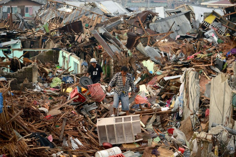 Men search for salvageable materials among destroyed houses in Tacloban, Leyte province, on November 26, 2013. The swift US humanitarian response to the devastation of Super Typhoon Haiyan highlights the need to expand America's military presence in the Philippines, Foreign Secretary Albert del Rosario said Monday. He said a proposed agreement to strengthen the US military presence, which was being negotiated as the storm struck on November 8, would allow for the easier delivery of relief aid by US forces in the future. (Noel Celis/Getty Images)