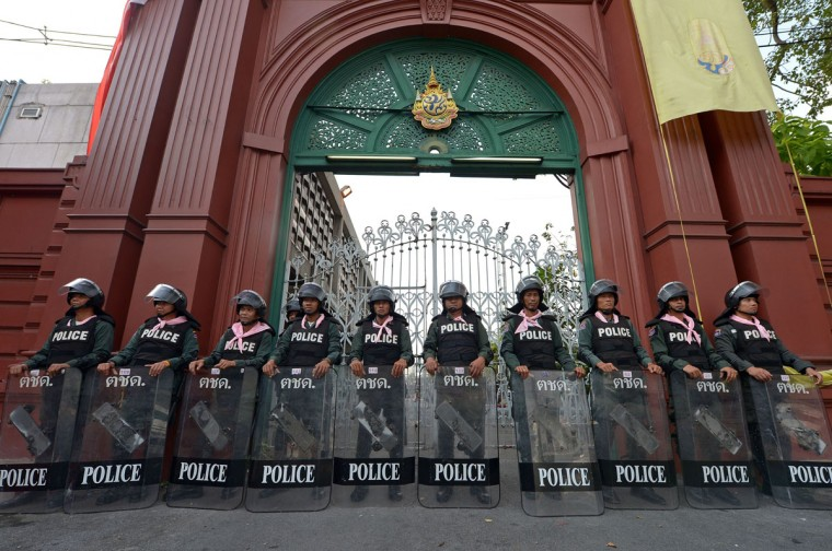 """Thai riot police stand guard outside the parliament as a no-confidence debate takes place inside the chamber in Bangkok on November 26, 2013. Thailand's premier appealed for an end to """"mob rule"""" as she prepared to face a no-confidence debate in parliament after protesters occupied key ministries in a bid to topple her government. (Pornchai Kittiwongsakul/AFP/Getty Images)"""
