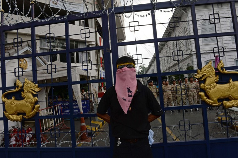 "A Thai opposition protester stands by a gate of the Interior Ministry where security forces (background) were deployed as demonstrators surround it in Bangkok on November 26, 2013. Thai opposition protesters besieged several more ministries in Bangkok on November 26 in a bid to topple the government, as Prime Minister Yingluck Shinawatra faced a no-confidence motion in parliament and warned against ""mob rule."" (Christophe ArchambaultAFP/Getty Images)"