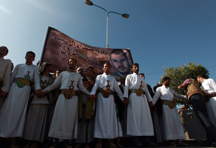 Yemeni mourners stand next to a poster of late Yemeni parliament member Abdul Karim Jadban during his funeral in Sanaa on November 26, 2013. The MP, who represented Zaidi Shiite rebels known as Huthis at a national dialogue, was assassinated on November 22 in the Yemeni capital. The murder comes as Huthi rebels have fought deadly clashes against hardline Sunni Muslim Salafists in the town of Dammaj in northern Yemen, where Shiites make up a majority in the mainly Sunni country. (Mohammed Huwais/AFP/Getty Images)