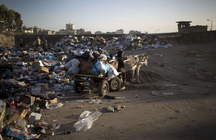 Palestinian workers of the Gaza City municipality use a donkey cart to collect rubbish from the Yarmuk waste dump area, in Gaza City, on November 26, 2013. The Hamas-run Gaza City municipality announced it was stopping working its waste cars due to a fuel shortage. (Mahmud Hams/AFP/Getty Images)