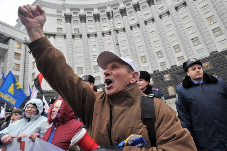 Protesters shout slogans on November 26, 2013 during a demonstration of pro-European activists in front of the Ukrainian government headquarters in Kiev. Pro-European Ukrainians staged the biggest protest rally in Kiev since the 2004 Orange Revolution, demanding that the government sign a key pact with the European Union. The opposition called the rally after President Viktor Yanukovych's government reversed a plan to sign a historic deal deepening ties with the European Union, in a U-turn critics said was forced by the Kremlin. (Genya Savilov/AFP/Getty Images)