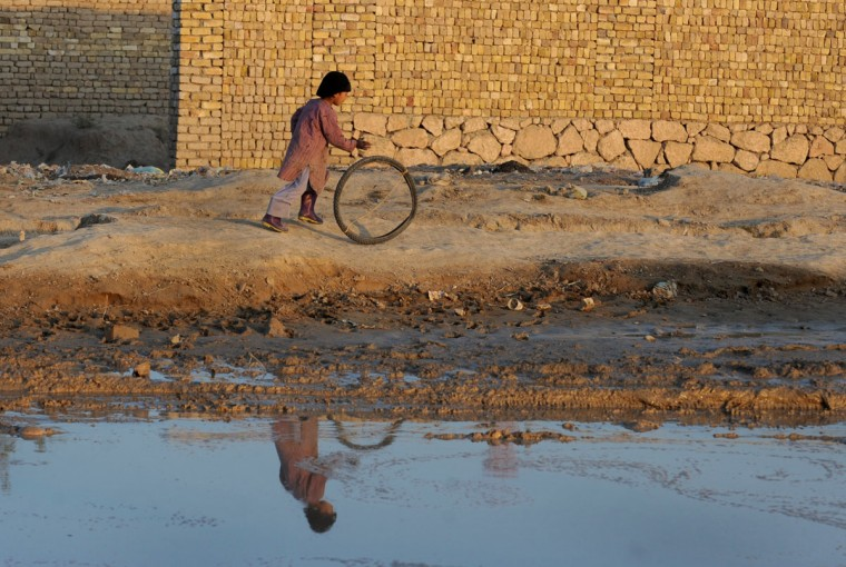An Afghan child plays with a tyre in Mazar-i Sharif on November 25, 2013. The war-torn country still faces poverty, unemployment and lack of infrastructure. (Farshad Usyan/AFP/Getty Images)